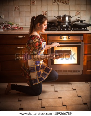 Young brunette woman holding pan with cookies near oven