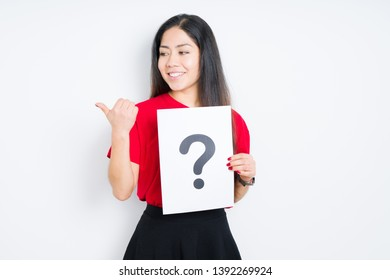 Young brunette woman holding paper with question mark over isolated background pointing and showing with thumb up to the side with happy face smiling