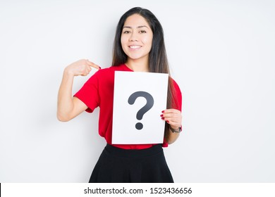 Young brunette woman holding paper with question mark over isolated background with surprise face pointing finger to himself