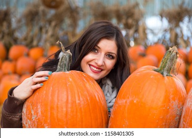 A young brunette woman holding a pumpkin in front of a row of pumpkins on a farm