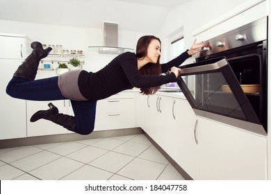 Young brunette woman in the kitchen levitating