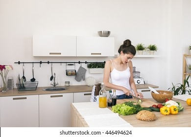 Young brunette woman at kitchen table preparing vegetables for salad