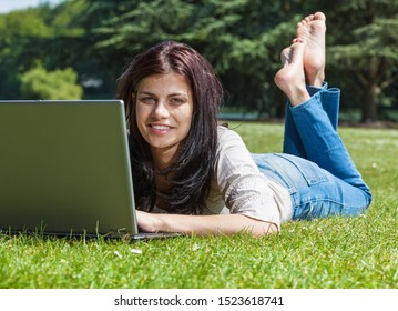 Young brunette woman with laptop computer lying on grass in a park