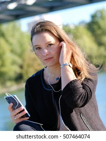 Young Brunette woman listening music with her ear and holding phone outside in the city near river and bridge