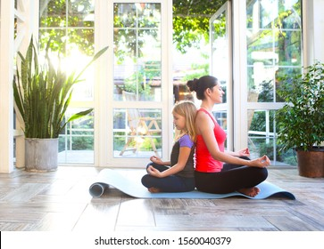 Young brunette woman with little daughter in a sporty uniform doing yoga on the terrace of a house by the garden