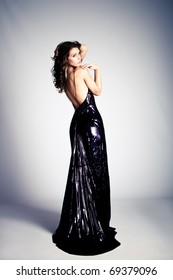 young brunette woman in long elegant dress, studio shot