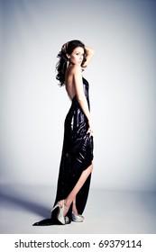 young brunette woman in long elegant dress, standing full body shot, studio shot