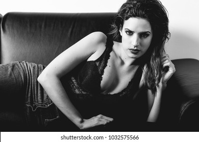 Young brunette woman looking at camera laying on a couch. Attractive girl, model of fashion in black lingerie. Black and white photograph.