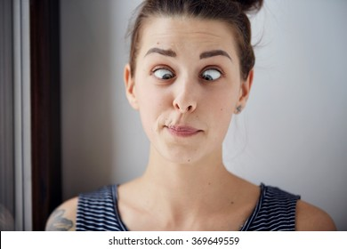 Young brunette woman looking cross-eyed. Closeup shot with wide angle and focus on the eyes. Harsh processing to emphasize the face structure. Human face expression body language reaction