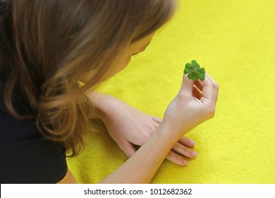 young brunette woman looking at a four-leaved cloverleaf in her hand, yellow background, focus on four-leaved clover
