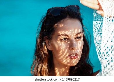 young brunette woman looking into the sun, using her boho style dress as sun cover