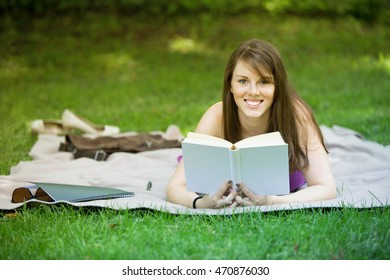 young brunette woman lying on blanket in park and reading a book