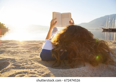Young brunette woman lying read a book on the beach