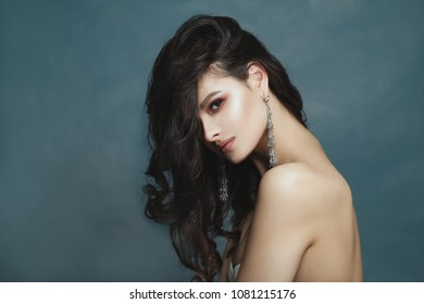 Young Brunette Woman with Makeup, Healthy Dark Wavy Hair and Silver Earrings with Semiprecious Stones on Blue Banner Background with Copy space