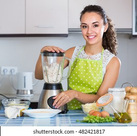Young brunette woman making croquettes using blender at home