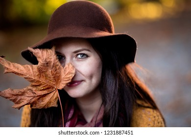 A young brunette woman with a maple leaf half covering her face.