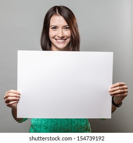 young brunette woman on grey background holding blank sign