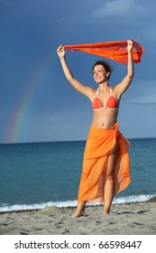young brunette woman in orange bikini and pareo holding scarf over her head and smiling, rainbow