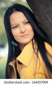 Young brunette woman outdoor.  Portrait of beautiful elegant woman  in autumn park looking away