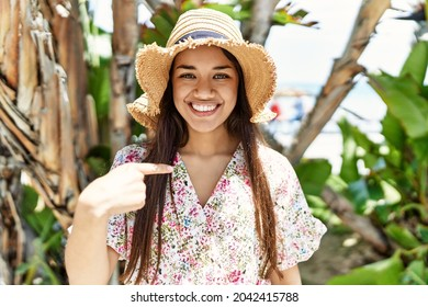 Young brunette woman outdoors on a sunny day of summer screaming proud, celebrating victory and success very excited with raised arms