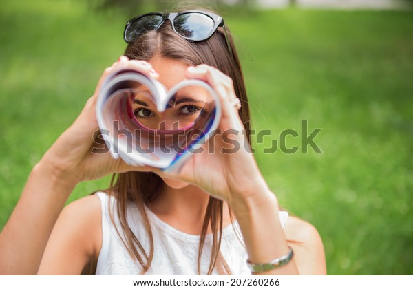 Eine junge Brünettenfrau im Freien in einem Park, die durch eine herzförmige Zeitschrift schaut