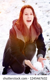 young brunette woman outdoors in the snow with snowball