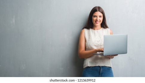 Young brunette woman over grunge grey wall using computer laptop with a happy face standing and smiling with a confident smile showing teeth