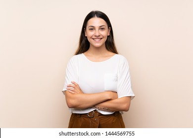 Young brunette woman over isolated background keeping the arms crossed in frontal position