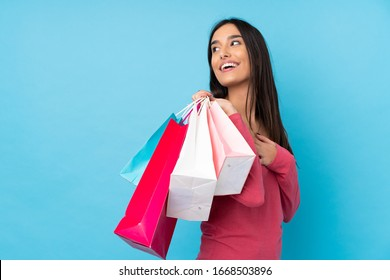 Young brunette woman over isolated blue background holding shopping bags and smiling
