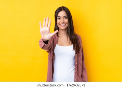 Young brunette woman over isolated yellow background counting five with fingers