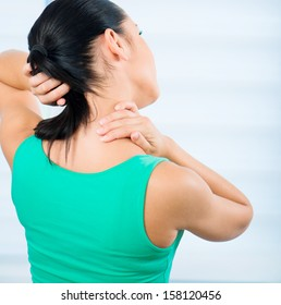 young brunette woman with a pain in the neck