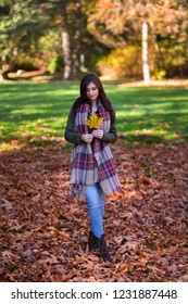 A young brunette woman in a park surrounded by fall leaves.