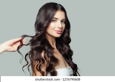 Young brunette woman with perfect hairstyle and female touching hand. Hair care and test concept
