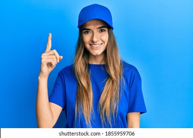 Young brunette woman with piercing wearing delivery uniform and cap happy face smiling with crossed arms looking at the camera. positive person.