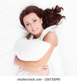 young brunette woman  with a pillow in bed at home, top view