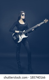 Young brunette woman playing bass