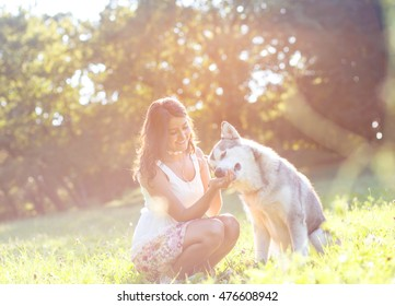 Young brunette woman playing with her dog in the park.