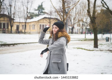 young brunette woman playing in park with snowball – joyful, youth, activity