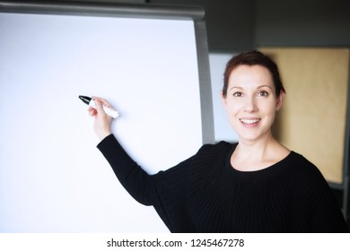 young brunette woman pointing at a flipchart in office
