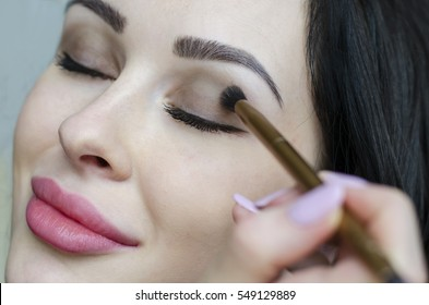 Young brunette woman putting make up on face with cosmetic brush