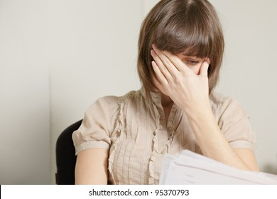 Young brunette woman reading report covering face with palm