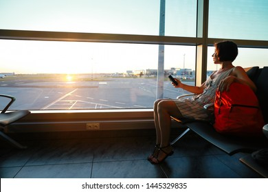 Young brunette woman with red backpack, awaits departure and looking  her smartphone with sunrise through the window