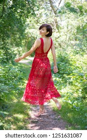Young brunette woman in a red dress walks in the summer forest