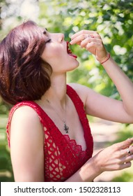 Young brunette woman in red dress eats red currant in the forest