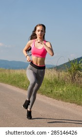 Young brunette woman running outdoors in sunny nature.