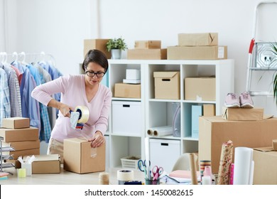 Young brunette woman sealing box with online order of client with cellotape while working in office