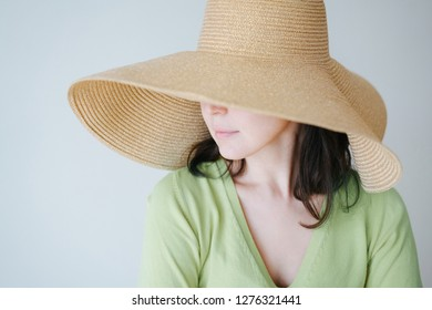 Young brunette woman with short hair in big floppy sun hat in green against white wall. Hat covers half of her face. Lips and nose. Head to side.