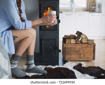Young brunette woman sitting by the fireplace in a wooden cabin