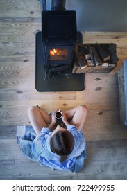 Young brunette woman sitting down on the floor by the fireplace in a wooden cabin. Top view from above