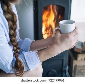 Young brunette woman sitting down on the floor by the fireplace in a wooden cabin